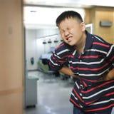Den asiatiska pojken med ett buk- smärtar Arkivfoton