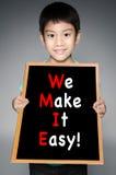 Den asiatiska pojken med GÖR VI IT LÄTT! meddelande på svart bräde royaltyfri fotografi