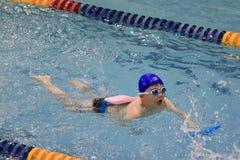 Den asiatiska pojken simmar Arkivbild