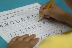 Den asiatiska pojken skriver bokstavsG med en gul blyertspenna Royaltyfri Foto