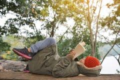 Den asiatiska pojken som läser en bok parkerar på Arkivbilder