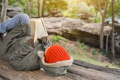 Den asiatiska pojken som läser en bok parkerar på Royaltyfria Foton
