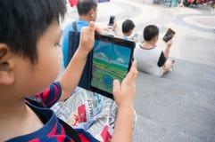 Den asiatiska pojken som spelar en Pokemon, går leken, på som jag vadderar mini2 Fotografering för Bildbyråer