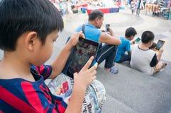 Den asiatiska pojken som spelar en Pokemon, går leken, på som jag vadderar mini2 Arkivbild