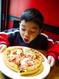 den asiatiska pojken äter pizza som är klar till Royaltyfria Bilder