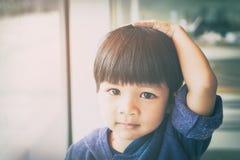 Den asiatiska pojken trycker på hans huvud och hår royaltyfria bilder