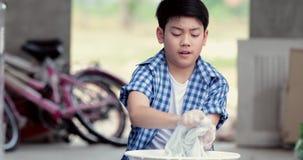 Den asiatiska pojken tvättar hans handduk vid handen stock video