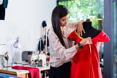 Den asiatiska skräddaren justerar plaggdesign på skyltdocka Royaltyfria Bilder