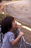 Den asiatiska små flickan riktar ett leende till familjen Arkivfoto