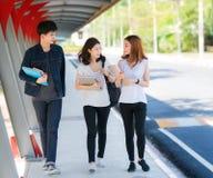 Den asiatiska studenten i universitetlek, går och talar togater på gångbanan Royaltyfri Bild