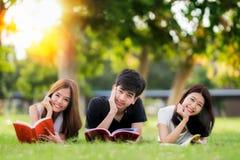 Den asiatiska studenten och vännen kopplar av och läser en bok i universitet Royaltyfria Foton