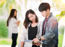 Den asiatiska studenten och vänner ser en rapport och returnerar arbete Royaltyfri Fotografi