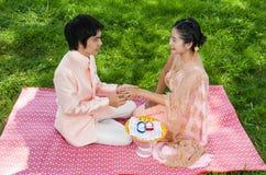 Den asiatiska thailändska brudgummen bär vigselringen till hans brud i thailändsk ceremoni Arkivfoton