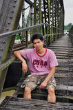 Den asiatiska Thailand mannen sitter på bron Royaltyfri Foto