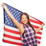 Den asiatiska tonårs- flickan rymmer amerikanska flaggan bak henne Royaltyfri Bild