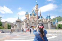 Den asiatiska turisten tar ett foto framme av en Disneyland slott i Hong Kong royaltyfria bilder