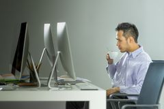 Den asiatiska unga affärsmannen sitter på datorskärmen på ett D arkivbilder