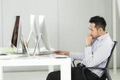 Den asiatiska unga affärsmannen sitter på datorskärmen på ett D royaltyfri bild
