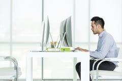 Den asiatiska unga affärsmannen sitter på datorskärmen på ett D royaltyfri fotografi
