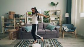 Den asiatiska unga damen är modern teknologi för enjoyig som lyssnar till musik i trådlös hörlurar och dansar den robotic dammsug arkivfilmer