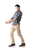 Den asiatiska unga grabben bär eller tar något Arkivbild