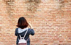 Den asiatiska unga kvinnan fotograferar en tegelstenvägg För henne cros arkivfoto