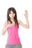 Den asiatiska unga kvinnan ger en gest av svär Royaltyfria Bilder