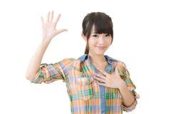 Den asiatiska unga kvinnan ger en gest av svär Royaltyfri Fotografi
