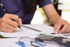 Den asiatiska unga kvinnan i blått arbete för skjortainnehavpenna, beräknar skattledning till likvideringen royaltyfri bild