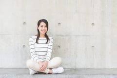 Den asiatiska unga kvinnan sitter royaltyfri bild