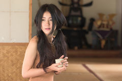 Den asiatiska unga kvinnan sitter i Japan stilrum Royaltyfri Foto