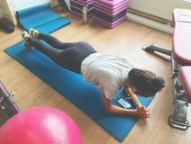 Den asiatiska unga kvinnan som övar plankan, poserar i idrottshallen Konditionlivsstilfoto av den aktiva flickan som önskar att f Arkivbild