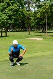 Den asiatiska unga mannen knäfaller, blicken på golfboll, medan golfspelet horizo royaltyfri bild