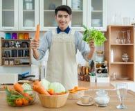 Den asiatiska unga mannen lagar mat Arkivfoto