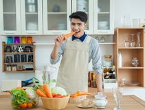 Den asiatiska unga mannen lagar mat Fotografering för Bildbyråer