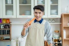 Den asiatiska unga mannen lagar mat Royaltyfria Bilder