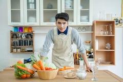 Den asiatiska unga mannen lagar mat, ståenden av den unga mannen som ser recept Arkivbilder
