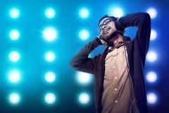Den asiatiska unga mannen lyssnar till musik via headphonen Royaltyfri Foto