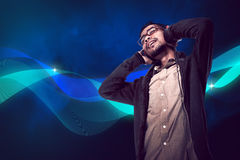 Den asiatiska unga mannen lyssnar till musik via headphonen Arkivbild