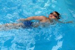 Den asiatiska ungen simmar i simbassäng - stil för den främre krypandet tar djup andedräkt Arkivbilder