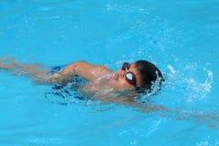 Den asiatiska ungen simmar i simbassäng - stil för den främre krypandet tar djup andedräkt Arkivfoton