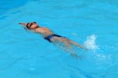 Den asiatiska ungen simmar i simbassängen - sparkstil för tillbaka slaglängd Arkivfoto