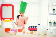 Den asiatiska ungen som har gyckel med matlagning och förbereder degen, bakar kakor i köket arkivfoto
