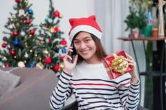 Den Asien kvinnan bär den santa hatten och att rymma gåvaasken och använder mobilt samtal med vännen och att sitta på soffan i ju royaltyfria foton