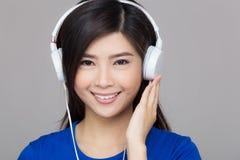 Den Asien kvinnan lyssnar till musik Arkivfoto