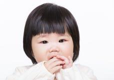 Den Asien lilla flickan suger fingret arkivfoto
