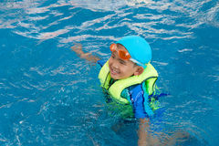 Den Asien pojken har gyckel i simbassäng royaltyfri foto