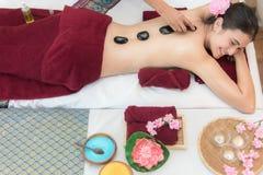 Den Asien skönhetkvinnan som ner ligger på massagesäng med traditionella varma stenar längs ryggen på den thailändska brunnsort-  royaltyfri bild