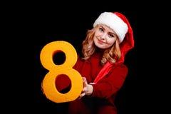 Den Attracive flickan i jultomten kostymerar att rymma ett nummer åtta på en svart bakgrund 2018 fira begrepp Royaltyfri Foto