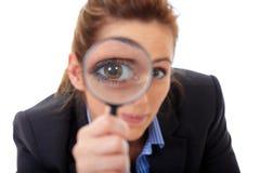 Den attraktiva affärskvinnan rymmer förstoringsglaset Arkivfoton